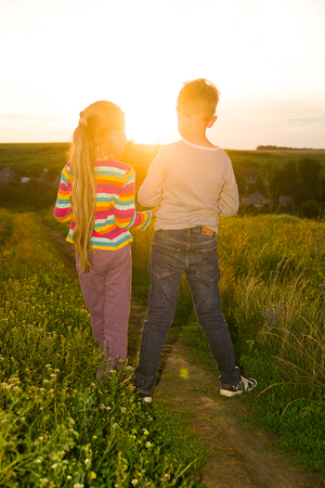 lass: Boy and girl holding hands and walking along the road at sunset Stock Photo