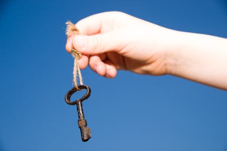 uncover: Child hand holding an old key on a string against the sky Stock Photo