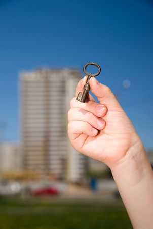 pack string: Child hand holding an old key on a string against the sky Stock Photo