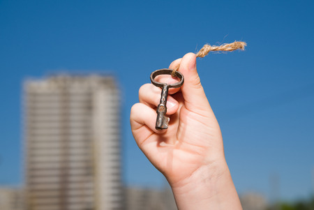 old key: Child hand holding an old key on a string against the sky Stock Photo