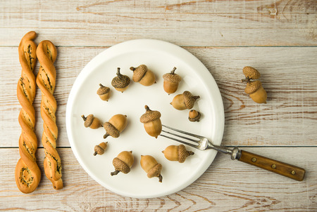 banket: Acorns on a plate, fork and bread on the table
