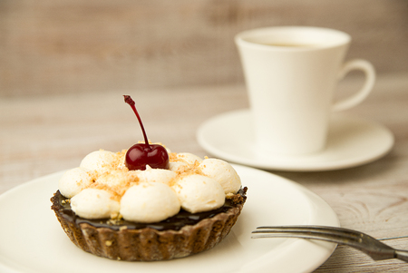 goody: Cake with a cherry and white cup on the table
