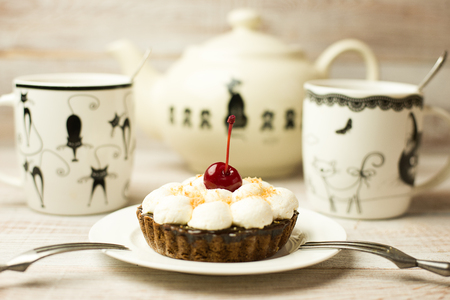grapnel: Two Cup of tea and cake with a cherry on the table