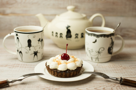 grapple: Two Cup of tea and cake with a cherry on the table