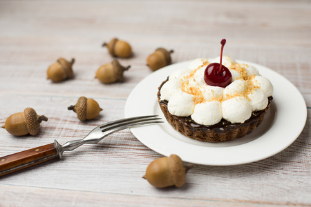 bap: Cake with cream and cherry on the acorns on the table Stock Photo
