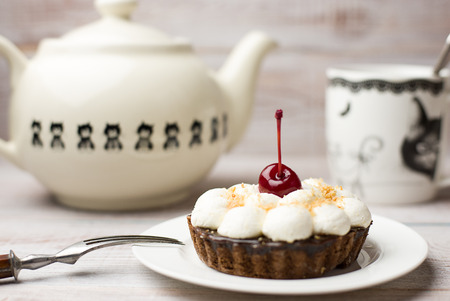 grapnel: Cup, tea and cake with a cherry on the table Stock Photo