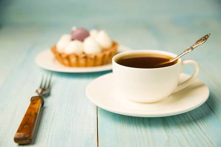 goody: Cake with cream and white cup on the table Stock Photo