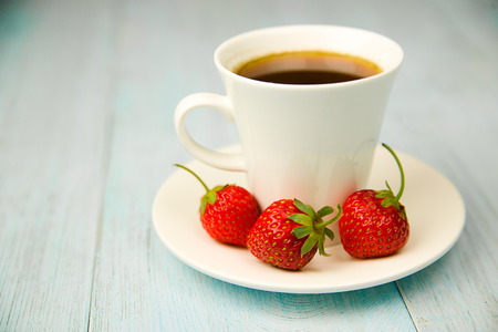 quencher: Cup and strawberry on over blue Stock Photo