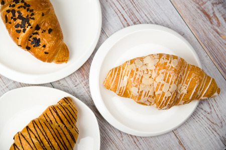 gratification: Three croissants on a white plate on the table