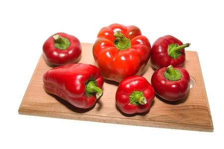 heartiness: Several ripe peppers on a wooden cutting board.