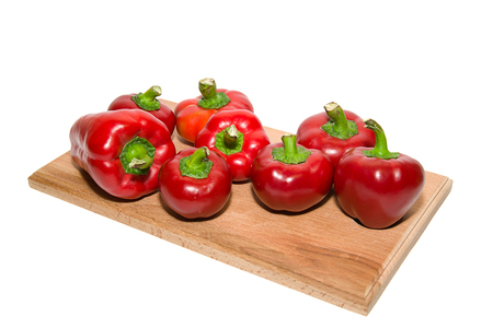 soundness: Several ripe peppers on a wooden cutting board.