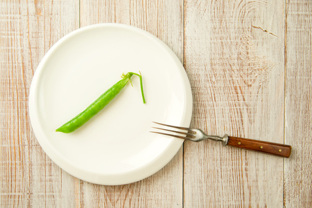 disclose: Green pea pod and fork on the white plate. Stock Photo