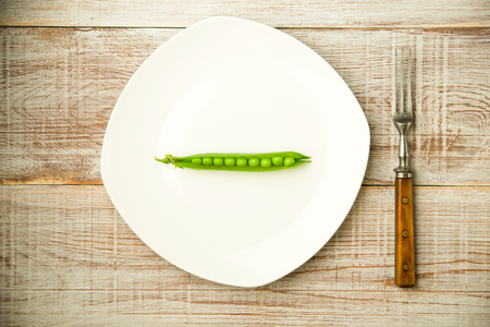 disclose: Opened green pea pod on the white plate.