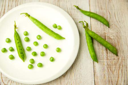 disclose: Opened green pea pods on the white plate. Stock Photo
