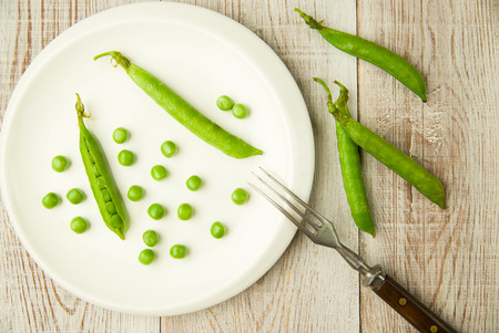 unfold: Opened green pea pods on the white plate. Stock Photo