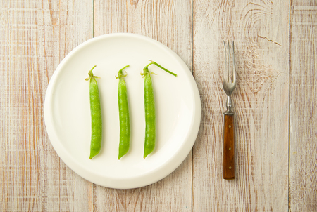 disclose: Green pea pods and fork on the white plate.