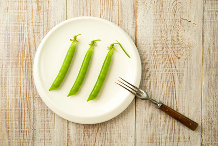 unfold: Green pea pods and fork on the white plate.