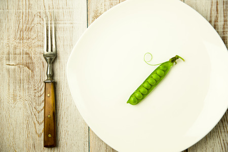 pea pod: Green pea pod and fork on the white plate. Stock Photo