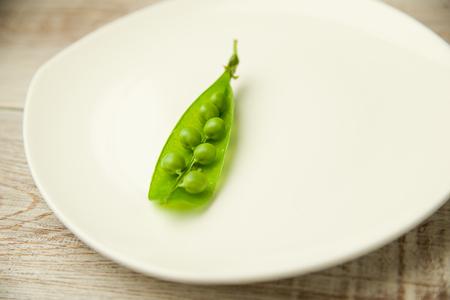 pea pod: Green pea pod on the white plate. Stock Photo