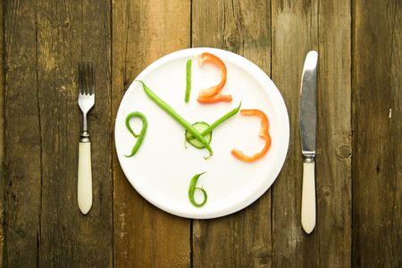 regimen: Watch made from vegetables are on a white plate