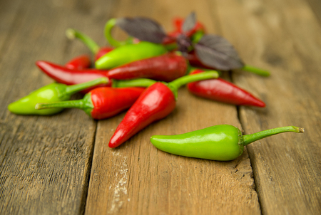 poignant: A few Chilli peppers on old wooden surface