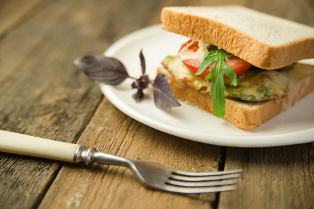 Sandwich with cutlet and vegetables on a white plate