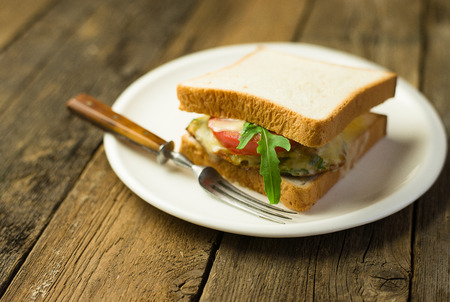 snacking: Sandwich with cutlet and vegetables on a white plate