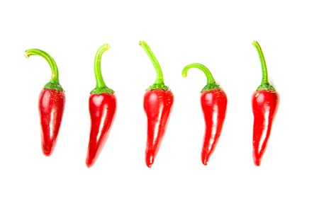 poignant: Five  ripe red Chilli peppers on over white