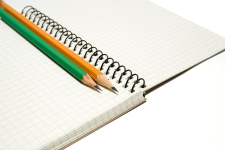 Opened notebook with a blank sheet and pencils on over white