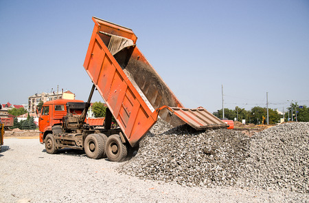 refurbishment: The truck pours the crushed body on the road construction