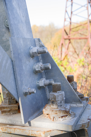 metal fastener: The iron base supports the power line is fixed by the bolt and nut. Stock Photo