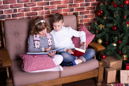 lass: Boy and girl reading book on the sofa near the Christmas tree