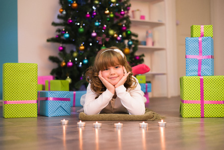 Smiling girl lying on the floor next to the presents and a tree Stock Photo