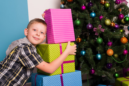 christmas ornamentation: Smiling boyl sitting on the floor next to the presents and a tree Stock Photo