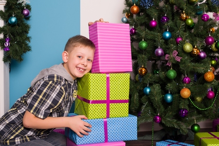 Smiling boyl sitting on the floor next to the presents and a tree Stock Photo