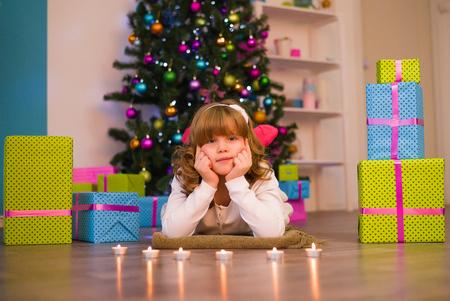 Girl lying on the floor among the gifts near the Christmas tree Stock Photo