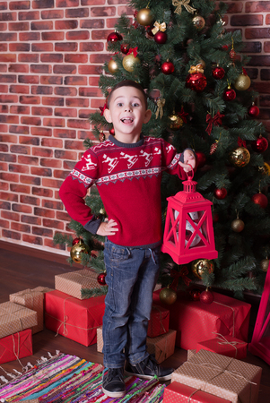 Smiling boy standing on the floor next to the presents and a tree Stock Photo