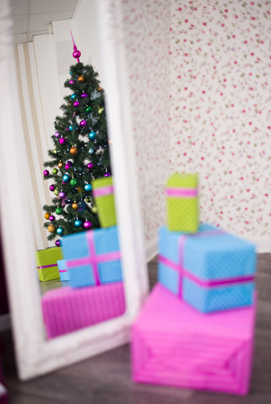 Christmas gifts and tree reflected in the mirror