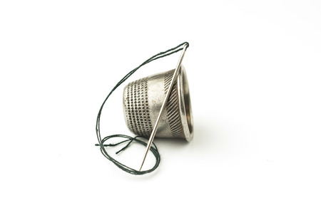 needlewoman: Metal thimble and needle with thread on over white Stock Photo