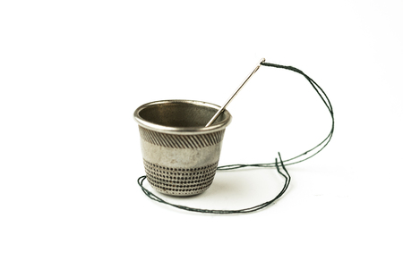 Metal thimble and needle with thread on over white Stock Photo