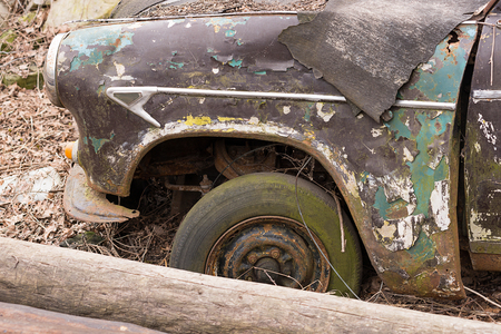 infirm: Wheel of an old car, which is under the open sky.