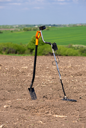 The metal detector and shovel are on the field Stock Photo