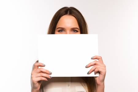 The girl is holding a sheet of paper in front of her