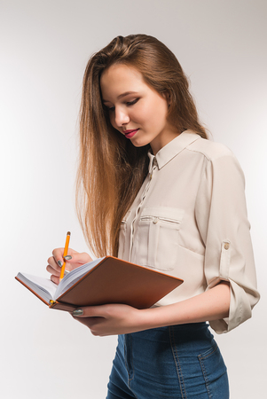 Girl with pencil and book in hands Stock Photo