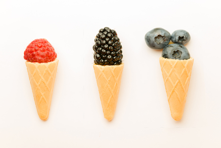 caller: Ripe berries are presented in the form of ice cream cones on white. Stock Photo