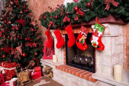 Many boxes with Christmas presents under the Christmas tree near the fireplace.