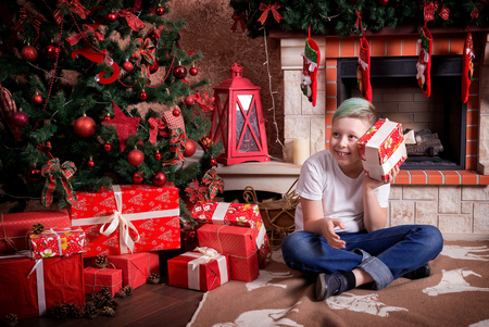 A child with a gift sits near a Christmas tree