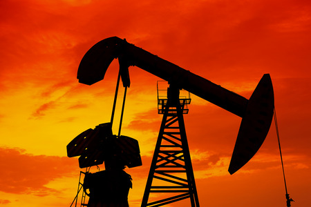 mechanical works: silhouette of the oil pump in evening