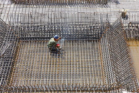 reinforcement: worker in the construction site making reinforcement metal framework for concrete pouring Editorial