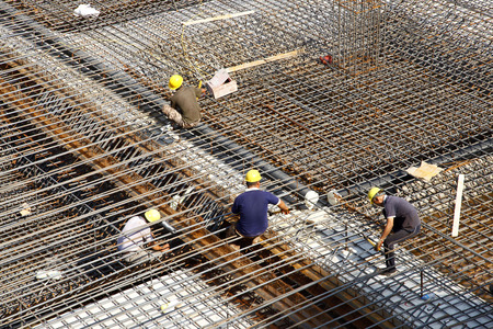 construction material: worker in the construction site making reinforcement metal framework for concrete pouring Stock Photo